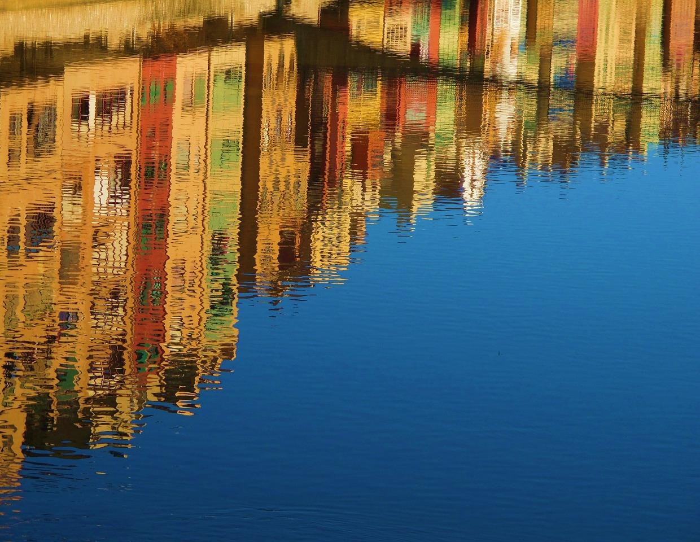 En bild av en vattenyta som speglar stadsbebyggelse i varma färger.